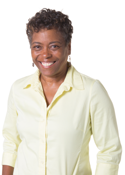 Middle aged business owner smiling, wearing yellow dress shirt.